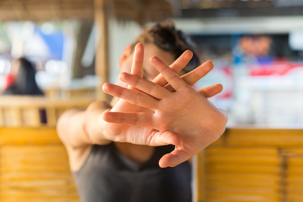 Young woman hide her face with hand. Focus on fingers.